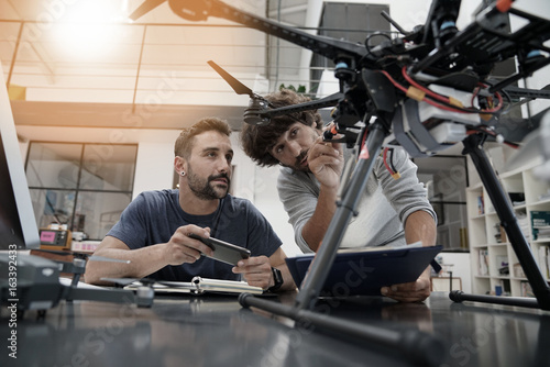 Fototapeta Engineer and technician working together on drone in office obraz
