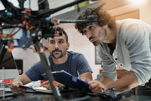 Photo Engineer and technician working together on drone in office