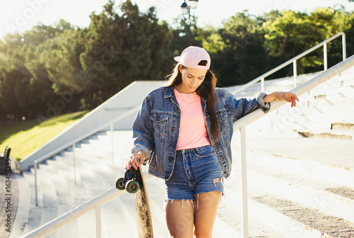 Fotografie, Obraz  Young girl with longboard in the park at sunrise or sunset