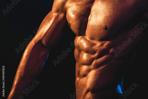Cuadros en Lienzo  Chest, arm and abs of young athlete close up