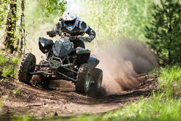 Fototapeta ATV rider creates a large cloud of dust and debris on sunny day