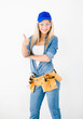 Beautiful young woman contractor with toolbelt showing thumbs up