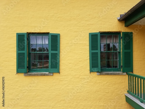 yellow building with green shutters