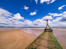 Red Buoy And Green Seaweed Wall On Beach With Blue Sky And White Fluffy Cloud