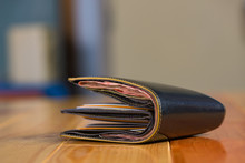 Black Men Leather Wallet With Banknotes On Wooden Table In Vintage Tone.