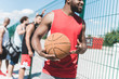 partial view of african american basketball player holding ball