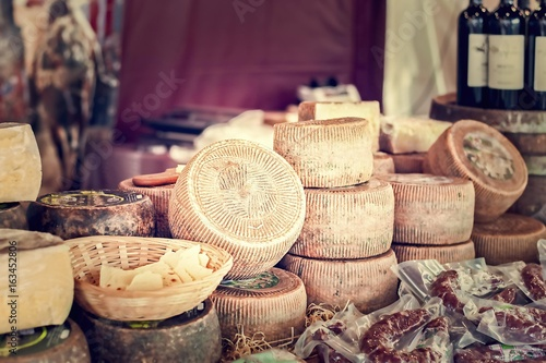 Photo sur Toile Produit laitier Cheeses and cut pieces on sale at market.