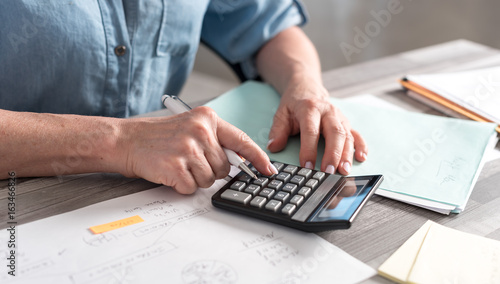 Fotografía  Female accountant using calculator