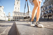 canvas print picture Tourist holding a photo camera on the saint Bavo square in Gent city in Belgium. Close-up view on the legs and camera