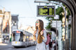 canvas print picture Young woman standing on the tram station with time table in the old town of Gent city in Belgium