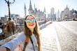 canvas print picture Young woman tourist making selfie photo standing on the bridge with beautiful view on Gent city in Belgium