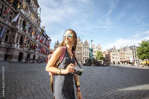 In de dag Antwerpen Young woman tourist with photo camera walking on the Great Market square in Antwerpen city in Belgium