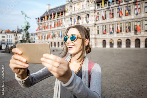 In de dag Antwerpen Young woman tourist making selfie photo with city hall on the background standing on the Great Market square in Antwerpen, Belgium