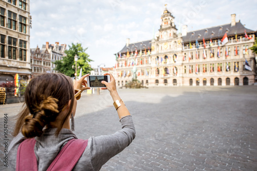 Poster Antwerp Young woman tourist photographing wiht phone on the Great Market square in Antwerpen, Belgium