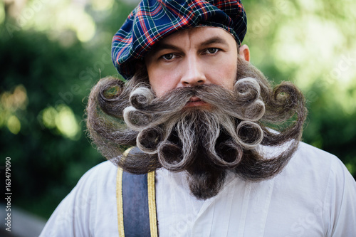 Foto Handsome portrait of a brave Scot with a amazing beard and mustache curls in the Hungarian style