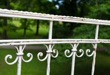 Old Aged Railing With Retro And Vintage Spiral Decoration. Green Grass And Trees In The Blurred Background