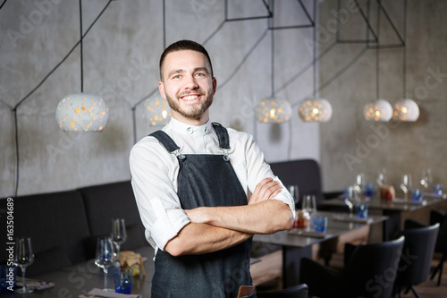 Fotobehang Restaurant A young, smiling waiter in a restaurant, standing next to the tables with a glass of wine. He wears an apron, looks confidently, folded arms over his chest