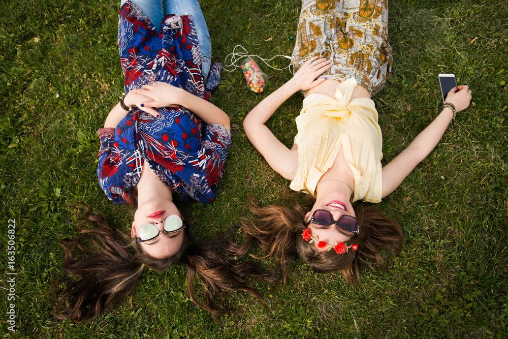 Fototapeta Happy girlfriends on a grass posing for a camera