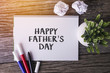 HAPPY FATHERS DAY word with Notepad and green plant on wooden background.