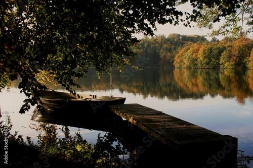 Plakat jezioro z pomostem i łodzią wiosną