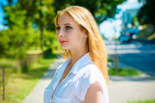 Young Sweet Blonde Girl In Casual Style Walk In Park And Feeling Beautiful