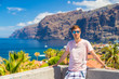 Young man standing by the Los Gigantes cliffs on Tenerife