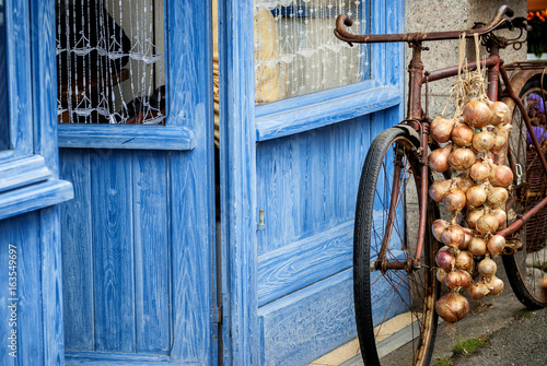 Fototapeta Bicycle with pink onion braid of Roscoff. Roscoff - Brittany - France obraz