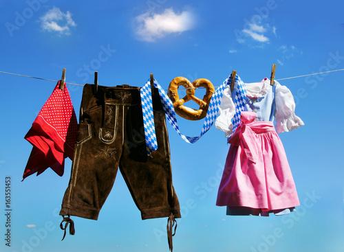 Fotografia  Fair, Oktoberfest, Volksfest, Dirndl und Lederhose hängen an Leine vor weiß-blau