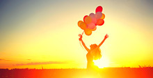 Beauty Girl Running And Jumping On Summer Field With Colorful Air Balloons Over Clear Sky