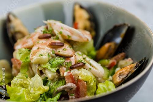 Cadres-photo bureau Nature Seafood salad with shrimps, calamari and mussels on marbel desk.