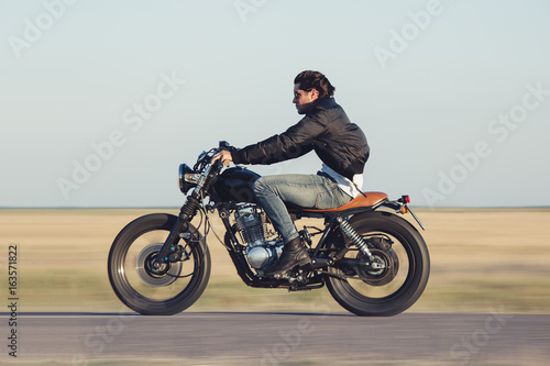 Photographie Young man riding a vintage motorcycle