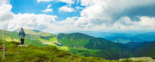 Fotografija  woman tourist stands on top of a mountain and enjoys a panorama of mountain ridg