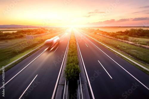 Fotobehang Nacht snelweg Highway landscape in a strong back light at sunset with motion blurred truck