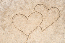 Two Hearts Drawing In Sand