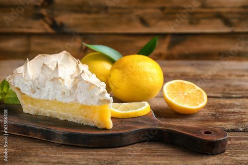 Fotografía  Piece of yummy lemon meringue pie on wooden table