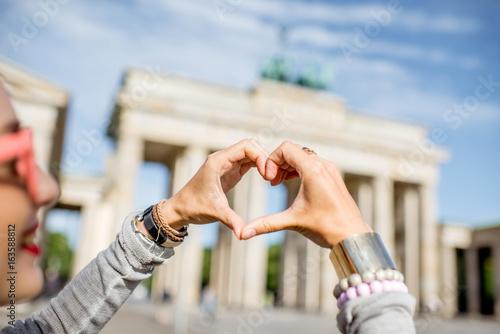 Obraz premium Młoda kobieta turystyczny kształt serca z rękami przed słynnymi bramami Brandenburgii w Berlinie
