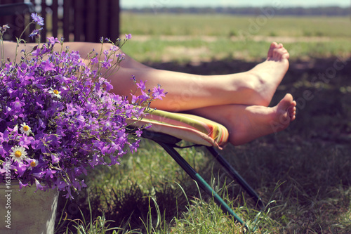 rest on vacation in the village/ large bouquet of wildflowers on a background of unrecognizable woman on a deck chair at summer day
