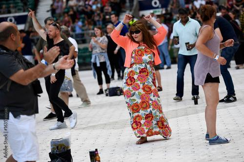 Fans dance as U2 perform during their U2: The Joshua Tree