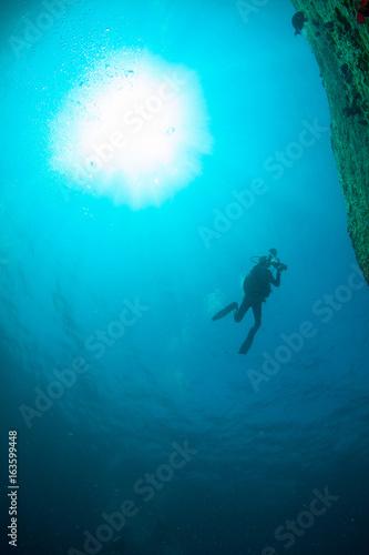 Fotobehang Duiken Scuba Divers, silhouettes against sunburst, in the ocean beside coral reef