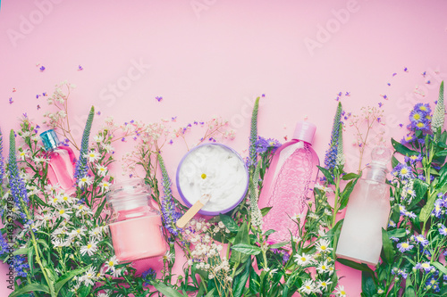Fotografía  Natural cosmetic products setting with fresh herbs and flowers on pink background, top view, border