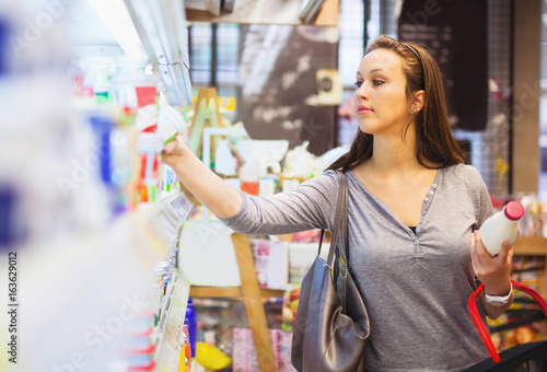 Fotografie, Obraz  Young woman buying milk in supermarket. Side view