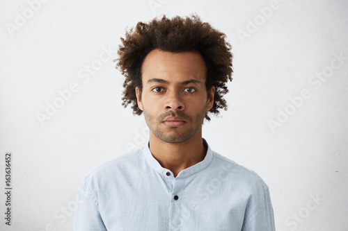 Canvastavla  Thinking black Afro American man with serious expression looking with dark narrow eyes directly into camera while posing against white studio wall