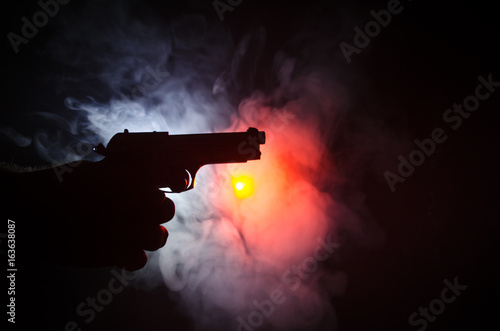 Obraz na plátně  Male hand holding gun on black background with smoke ( yellow orange red white )
