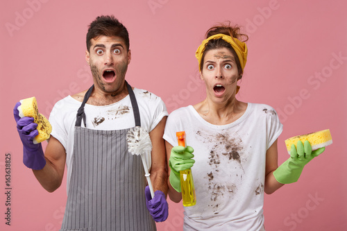 Fotografía  Handsome male wearing apron standing near his wife holding cleaning equipment having shocked look