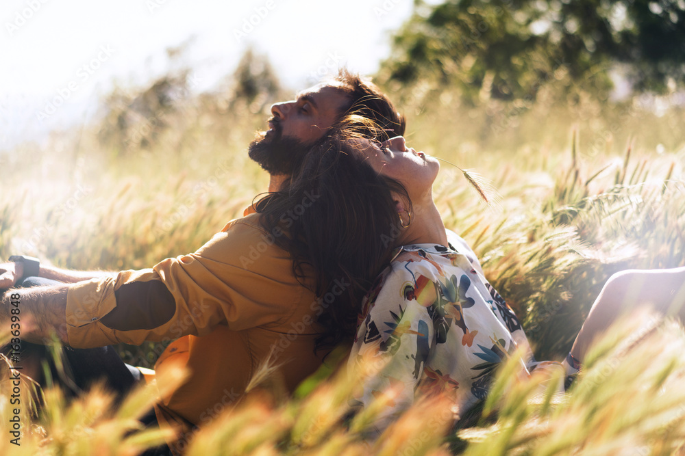 Fototapety, obrazy: A happy beautiful couple in love is sitting amidst the meadow on a warm sunny day. Romantic photo of a man and a woman sitting back-to-back on a grass. Weekend picnic dating outdoors.