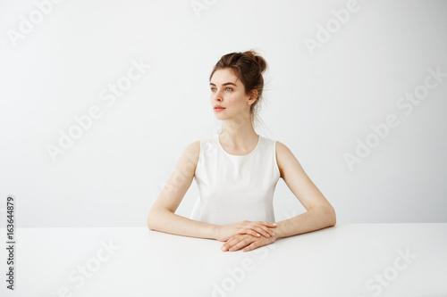 Fotografie, Obraz  Young beautiful brunette girl sitting at table straight over white background