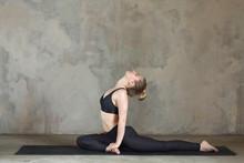 Young Woman Practicing Yoga One-Legged King Pigeon Pose, Eka Pada Rajakapotasana Against Texturized Wall / Urban Background