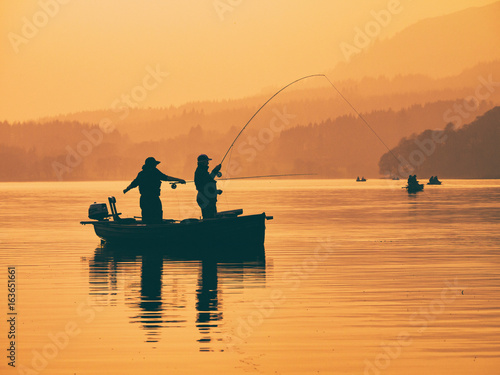Fototapeta Silhouette of man fishing on lake from boat at sunset