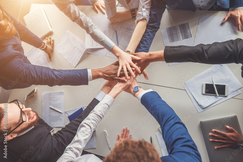 Fototapety, obrazy: Unity concept. Close-up of people holding hands together while sitting around the desk