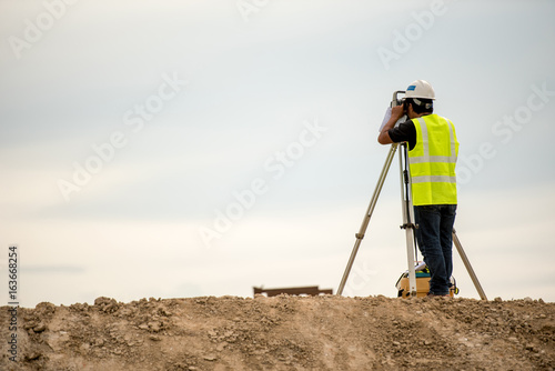 Valokuvatapetti survey engineer in construction site use theodolite mark a concrete pile co ordi